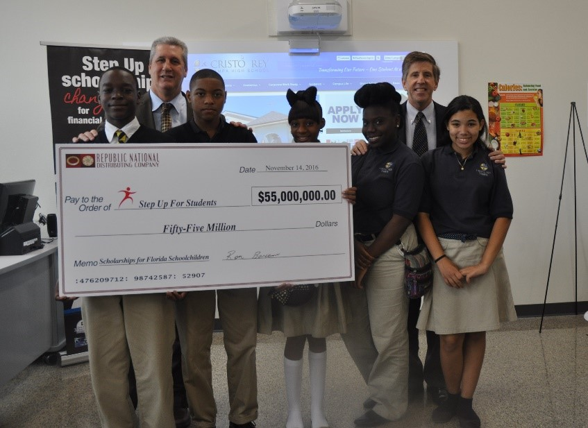 At an event on Monday, Republic National Distributing Company Florida EVP Ron Barcena (second from left) presented Step Up For Students with a $55 million check at an event at Cristo Rey Tampa High School. Joining Barcena is Step Up For Students President Doug Tuthill (scond from right) and Step Up scholars Jeremiah Alexander, Steven Faison, Tamara Gumbs, Ziyah Hughes and Ariely Burgos.